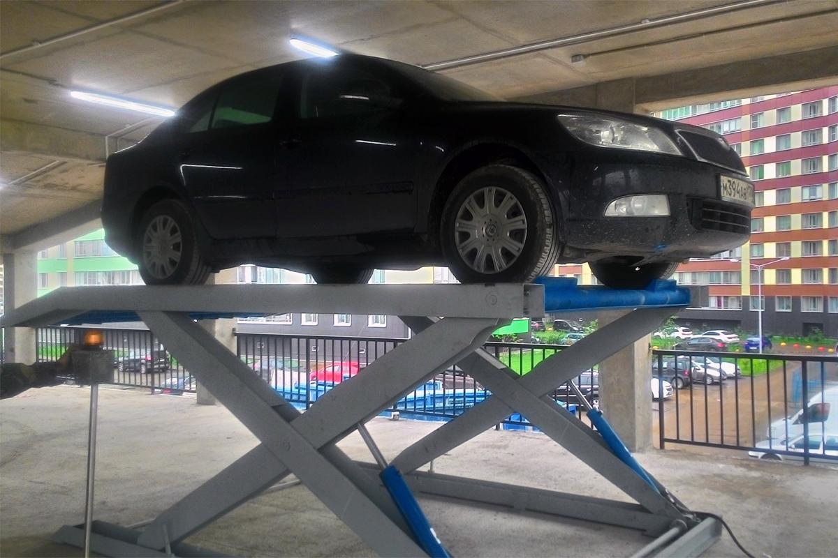 Автомобиль на верхнем уровне парковочного подъёмника ножничного типа