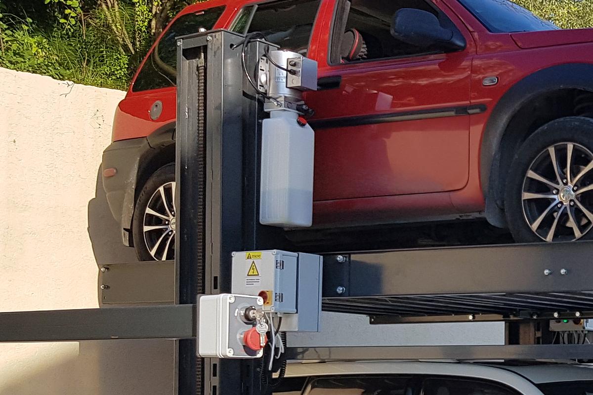 Гидроблок и блок управления парковочного подъёмника на уличной стоянке в Сочи